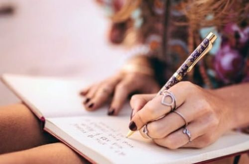 recorte de uma mulher sentada com um caderno abero no colo, escrevendo algo. plano principal caderno, folhas brancas e algum texto.
